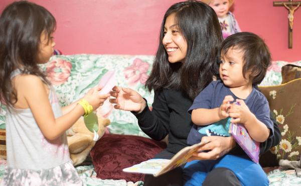 Sara Martín reads bedtime stories with her children. When the kids were younger, she says, staying up to date on their frequent immunizations was tough, because of cost and transportation issues.