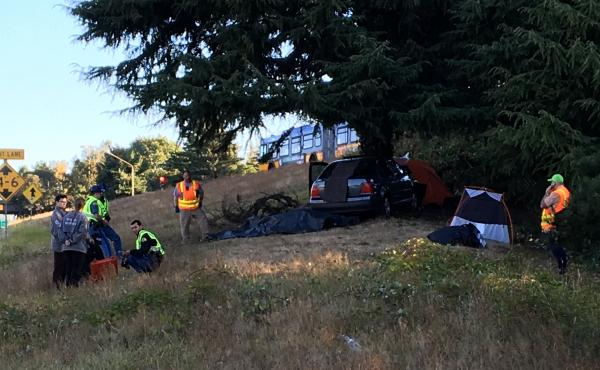 "Officials inspect the scene at the Seattle homeless camp known as ""the Jungle,"" where a car ran off the road and resulted in the death of a young man who was in his tent."