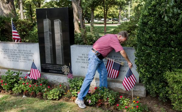 Russell Mercer replaces old U.S. flags with new ones at the Flushing World Trade Center Memorial at Flushing Cemetery in New York City. His stepson, Scott Kopytko, was killed on Sept. 11.