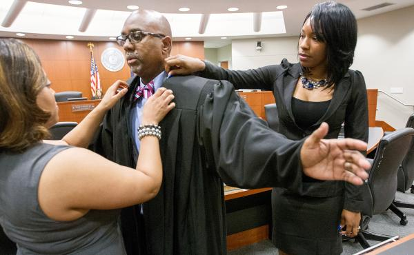 Judge Adrian Adams is helped with his robe by his daughters during a robing ceremony Friday in Gretna, La. Adams won a race for 24th Judicial District Court in November behind a campaign that raised a modest $22,350, including several four-figure donation