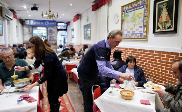 Volunteers serve free dinner to homeless people at Robin Hood restaurant in Madrid.