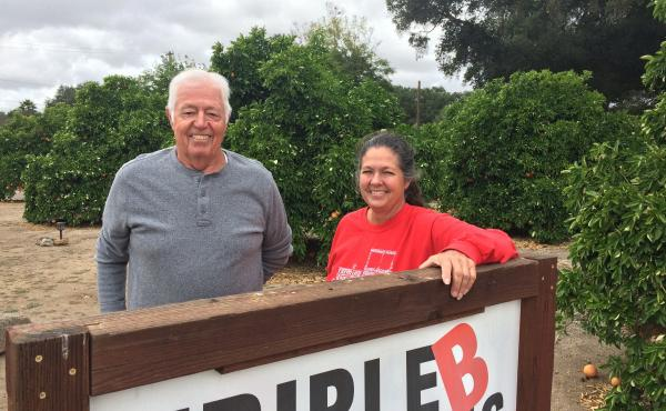 Gary Broomell and his daughter, Debbie, pose behind a sign on their ranch in San Diego County. Their family has been growing citrus for generations, but lately, it's been hard staying in the black growing oranges, so they started a vineyard a few years ag