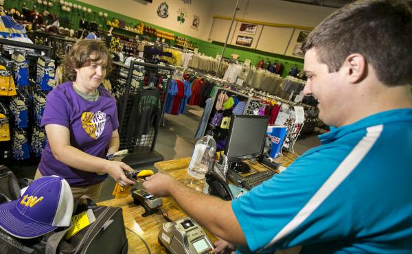 April Thompson makes a purchase at Legacy Team Sales in Ocala, Fla., in September. Economists say October's surprisingly strong job growth will encourage the Federal Reserve to hike interest rates next month. So holiday shoppers may pay more for using cre