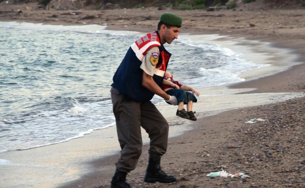 A Turkish paramilitary police officer carries the body of 3-year-old Syrian refugee Aylan Kurdi, found washed ashore near the Turkish resort of Bodrum in September 2015.