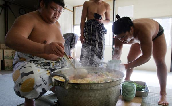 Sumo wrestlers serve up chanko-nabe at Musashigawa Sumo Stable in 2007 in Osaka, Japan.