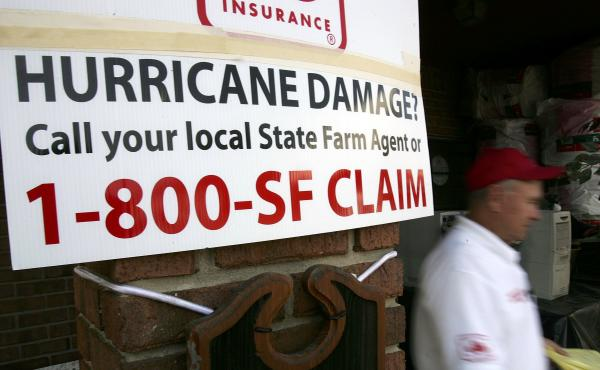 A banner for State Farm insurance in in D`Iberville, Miss., tells property owners the number to call after Hurricane Katrina hit in 2005.