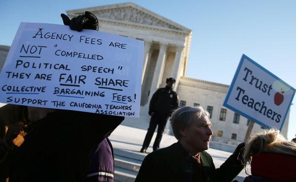 People for and against unions hold up signs Monday in front of the U.S. Supreme Court building in Washington. The court was hearing arguments in Friedrichs v. California Teachers Association. Justices will decide whether California and other states can ma