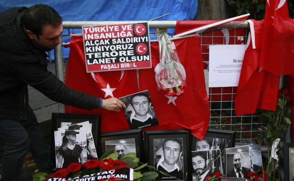 A man adjusts a victim's photograph displayed with floral tributes and Turkish flags outside the Reina nightclub following the attack in Istanbul earlier this month.