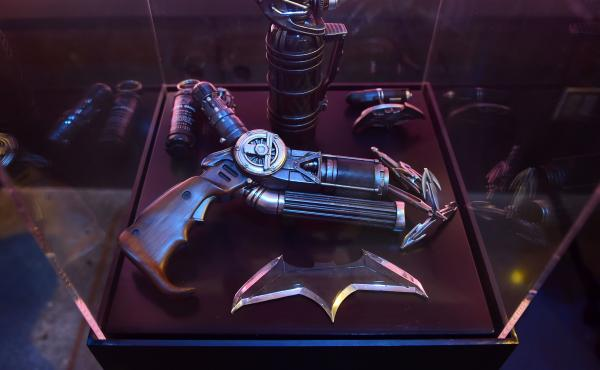 Batman's gun from Batman v Superman is displayed with a batarang and other weapons.