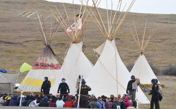 Law enforcement dressed in riot gear arrest protesters who are demonstrating against construction of the Dakota Access Pipeline near Cannon Ball, N.D. Police and National Guard moved in on an encampment of tents and teepees on Thursday.