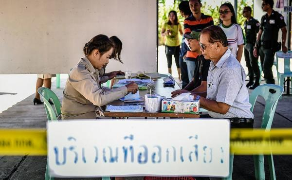 People register to vote at a polling station before casting their ballots in the constitutional referendum in Thailand's northeastern province of Buriram on Sunday.