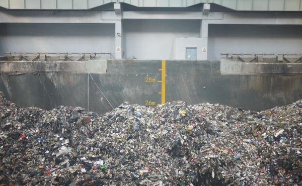 Inside Beijing's Gao'antun incinerator plant, garbage piles past the 25-meter (82-ft.) mark inside an arena-sized garbage container where engineers operate giant claws to sift through it.