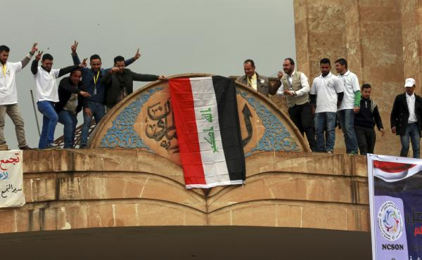 Students at Mosul University place the Iraqi national flag at the entrance on Sunday after it was liberated from Islamic State militants. The Iraqi military, supported by the U.S., has retaken the eastern part of the city. ISIS still holds the western par