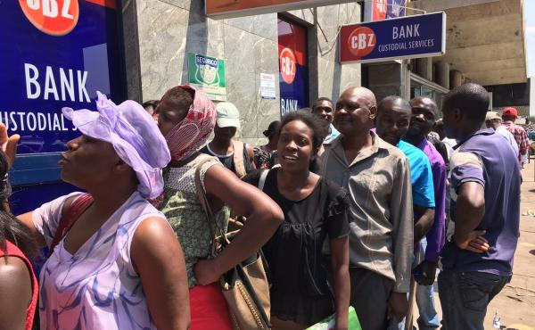 Zimbabweans stand in line for hours outside an ATM at a bank in Harare in order to withdraw U.S. dollars from their accounts. Many fear they will lose access to their dollars when the government introduces new bond notes it says will be equivalent to the