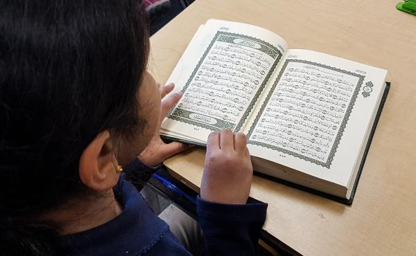 A third-grader reads from the Quran.