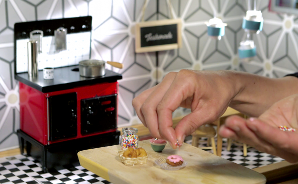 Human-sized hands make doll-sized doughnuts in the Tiny Kitchen — roughly 1/12 the normal size.