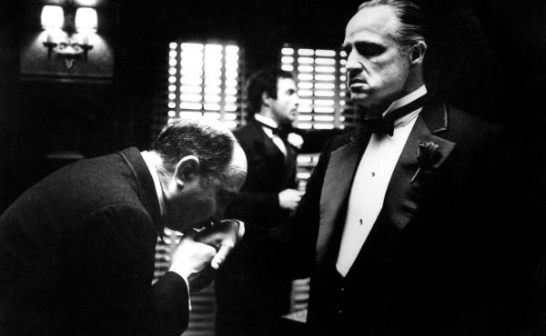 Amerigo Bonasera (Salvatore Corsitto) kisses the hand of Don Vito Corleone (Marlon Brando) in a scene from Francis Ford Coppola's The Godfather.
