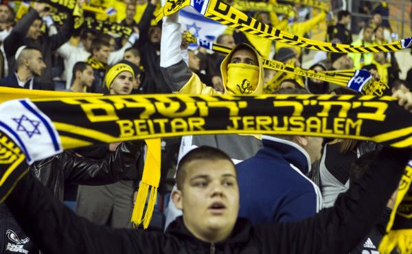 Fans of Beitar Jerusalem, often known as La Familia, hold up scarves during a match against Bnei Sakhnin at Teddy Stadium in Jerusalem. With a reputation for aggression and racist behavior, La Familia has come under the scrutiny of city leaders.
