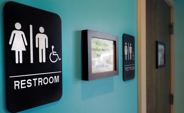Unisex signs hang outside bathrooms at Toast Paninoteca in Durham, N.C.
