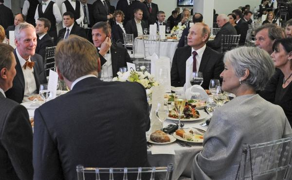 Russian President Vladimir Putin sits next to Flynn at an exhibition marking the 10th anniversary of RT (Russia Today) in Moscow on Dec. 10, 2015.
