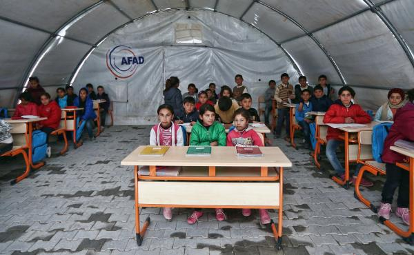 Syrian children listen to a teacher during a lesson in a temporary classroom in Suruc refugee camp on March 25 in Suruc, Turkey. The camp is the largest of its kind in Turkey with a population of about 35,000 Syrians who have fled the ongoing civil war in