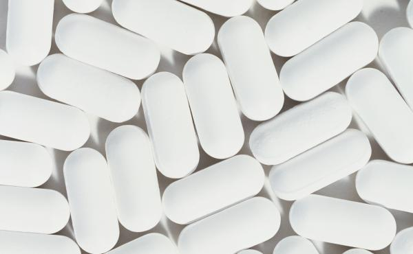 White pills on white background.
