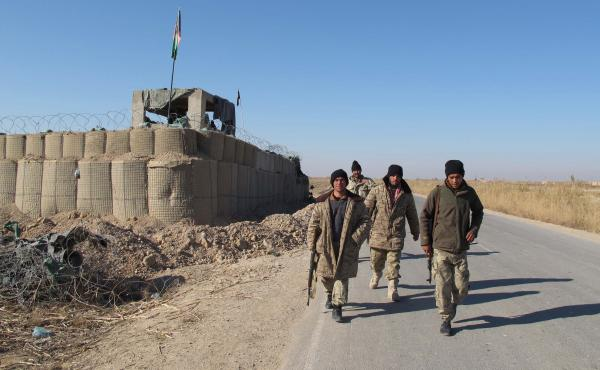 Afghan security forces patrol near their base in the Marjah district of Helmand province on Dec. 23. Dozens of Marines were killed in Marjah five years ago, and since then the Taliban have slipped back in. Now American forces are increasingly being drawn