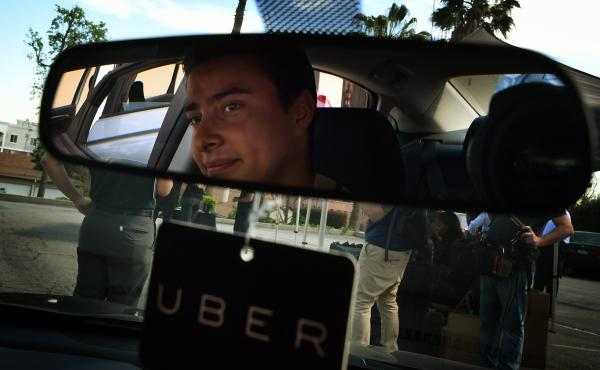 """Jesse Vega checks out a vehicle at an Uber """"Work On Demand"""" recruitment event March 10 in South Los Angeles. The company is researching ways to get rid of its surge pricing, a feature that drivers like but that can make costs unpredictable for consumers."""