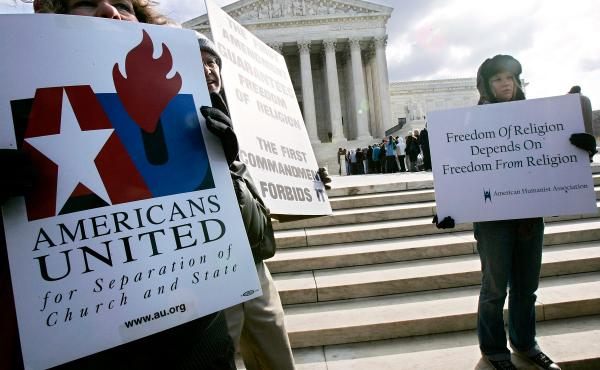 Activists hold posters during a March 2005 rally in front of the U.S. Supreme Court to support separation of church and state. The court heard two cases regarding whether Ten Commandments monuments should be displayed on government properties.