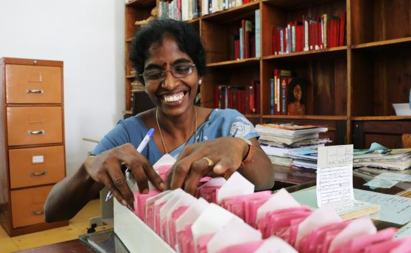 """Librarian S. Kalaivani has worked at the Jaffna Public Library in Sri Lanka for five years. """"I love working here,"""" she says. """"It's a pleasure to help the people who are continuing to get knowledge."""""""