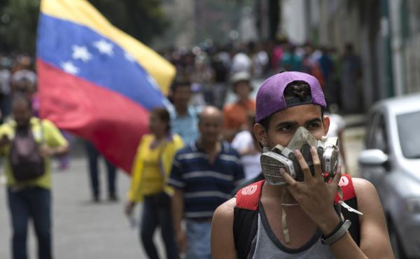 A protester wears a respirator mask during a demonstration against President Nicolas Maduro in Caracas, Venezuela, on May 18. Police used teargas against some demonstrators.