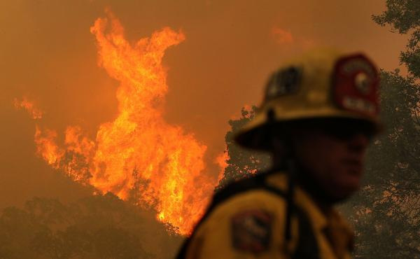 A firefighter monitors flames from the Rocky Fire as it approaches a home late last month. The wildfire has consumed thousands of acres in just over a week.