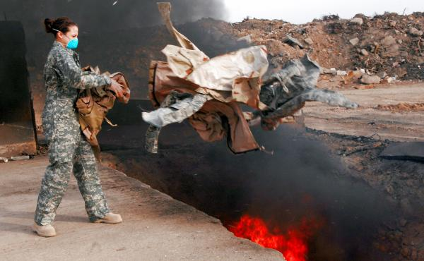 Senior Airman Frances Gavalis tosses unserviceable uniform items into a burn pit at Balad Air Base, Iraq in 2008. The military destroyed uniforms, equipment and other materials in huge burn pits in Iraq and Afghanistan. Some veterans say those pits are re