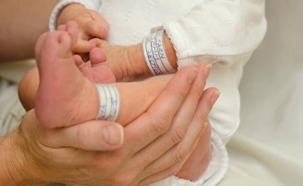Hands holding one week old baby boy.