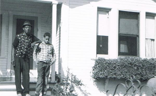 Author Walter Mosley in front of his childhood home in the LA neighborhood of Watts. He's standing with his father.