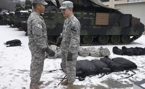 """An American soldier (right) from the First Armored """"Ironhorse"""" Brigade of the 1st Calvary Division is among those who began arriving in South Korea in mid-January. They are replacing U.S. troops that cycle out in February. He's speaking with a South Korea"""