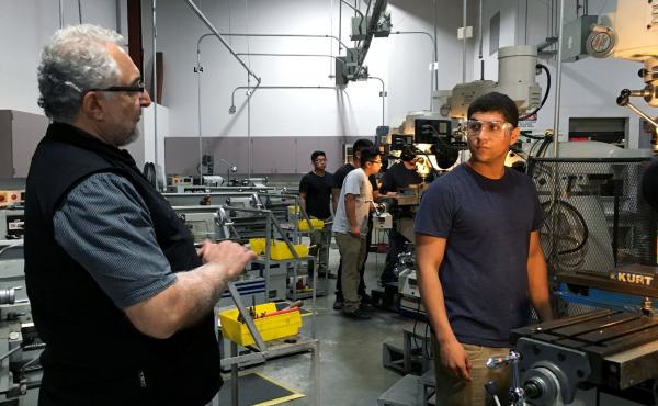 Professor Philip Yaghmai (left) talks to Ismael Becerra, 18, in the lab at El Camino Community College's Compton campus. Students translate machining theory into practice on vertical mills, CNC machines and other heavy equipment used in aerospace fastener
