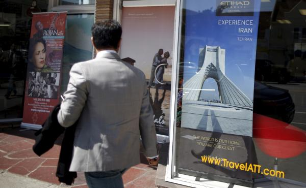 A man walks past a poster advertising travel to Tehran, Iran, in Los Angeles on July 14. A nuclear deal between Iran and six world powers lifts some sanctions against Iran, but most U.S. sanctions will remain in place.