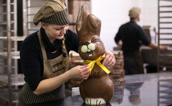 Employee Sandra Jaeckel adjusts a ribbon around the neck of a giant chocolate Easter bunny at the production facility of Confiserie Felicitas chocolates maker in Hornow, Germany, in 2014.