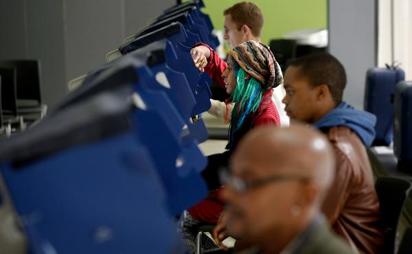 Voters cast their ballots during early voting at a polling station at Truman College in Chicago, Ill.