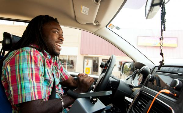 Emeka Nnaka, who uses a wheelchair, drives his new accessible van to meet a friend in Tulsa, Okla. The van allows the 27-year-old greater independence, making it easier to get to school and work and to have a social life. Six years ago, Nnaka, then a semi