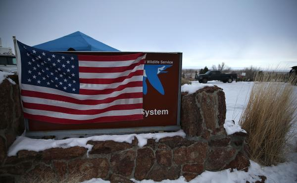 A U.S. flag hangs over a sign in front of the Malheur National Wildlife Refuge headquarters on Tuesday near Burns, Ore. An armed group has occupied the refuge since the weekend.