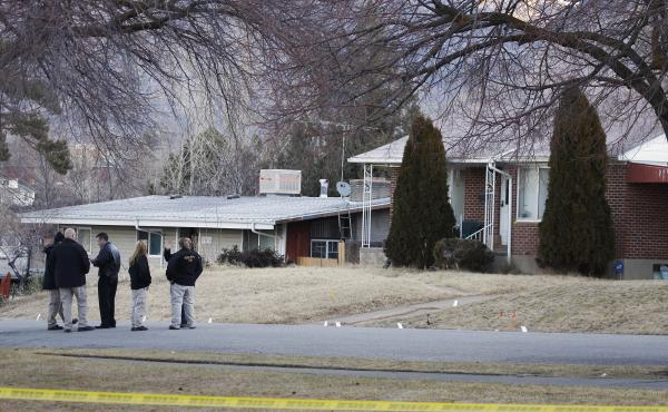 Investigators stand next to evidence markers in front of the house of Matthew Stewart, who was shot and injured by Ogden police during a drug raid, in Ogden, Utah, Jan. 5, 2012. One police officer was killed and five were wounded in the shootout that erup