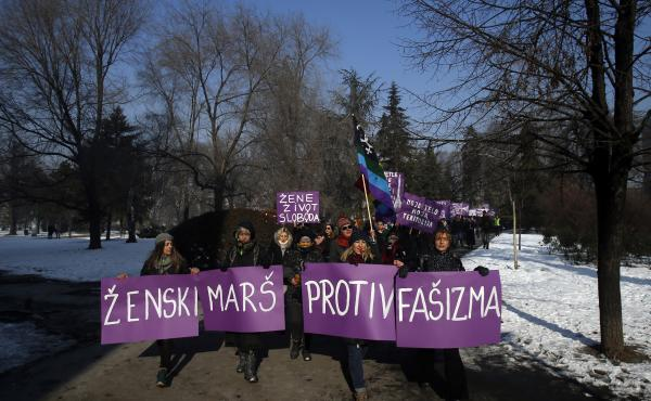 """Activists hold a banner that reads """"Women's March Against Fascism"""" during the Women's March rally in Belgrade, Serbia, on Saturday."""