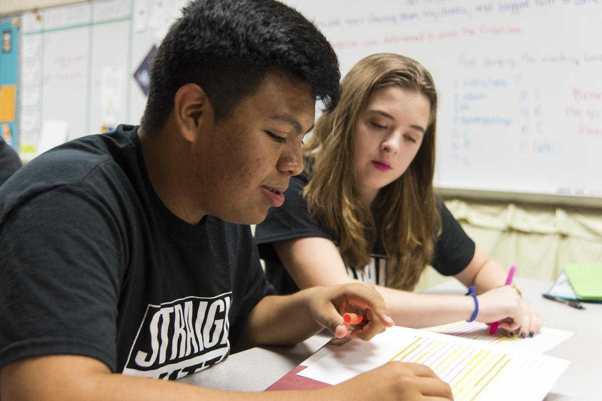 Jose talks with his fellow student Sydnee Outlaw about an assignment for their English class.