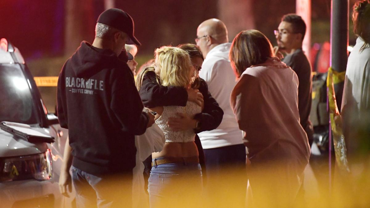 People comfort each other outside a bar in Thousand Oaks, Calif., where a gunman opened fire and killed 12.