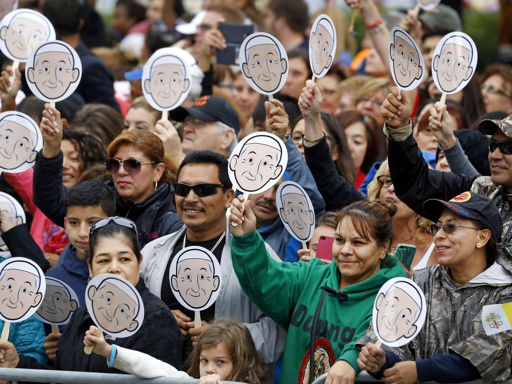 People wave images of Pope Francis as they wait for him to arrive for a Mass at the Cathedral Basilica of Saints Peter and Paul in Philadelphia, on Saturday.