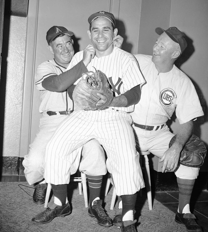 In 1955, Yogi Berra sat on the knees of two Hall of Fame catchers, Mickey Cochrane (left) and Gabby Hartnett at Yankee Stadium in New York City.