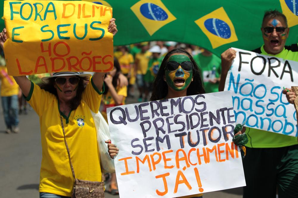 """A family carries posters with """"Dilma out and Impeachment Now,"""" written in Portuguese, during a protest Sunday in the capital, Brasilia."""