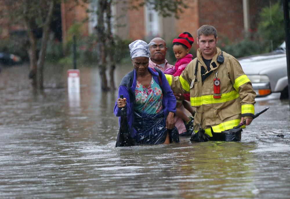 A member of the St. George Fire Department assists residents as they wade through floodwaters from heavy rains in Baton Rouge, La. on Friday.